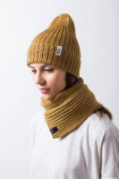 """Вязаная шапка тыковка и шарф на молодой девушке. Коллекция """"Камчатка"""". Цвет горчичный."""