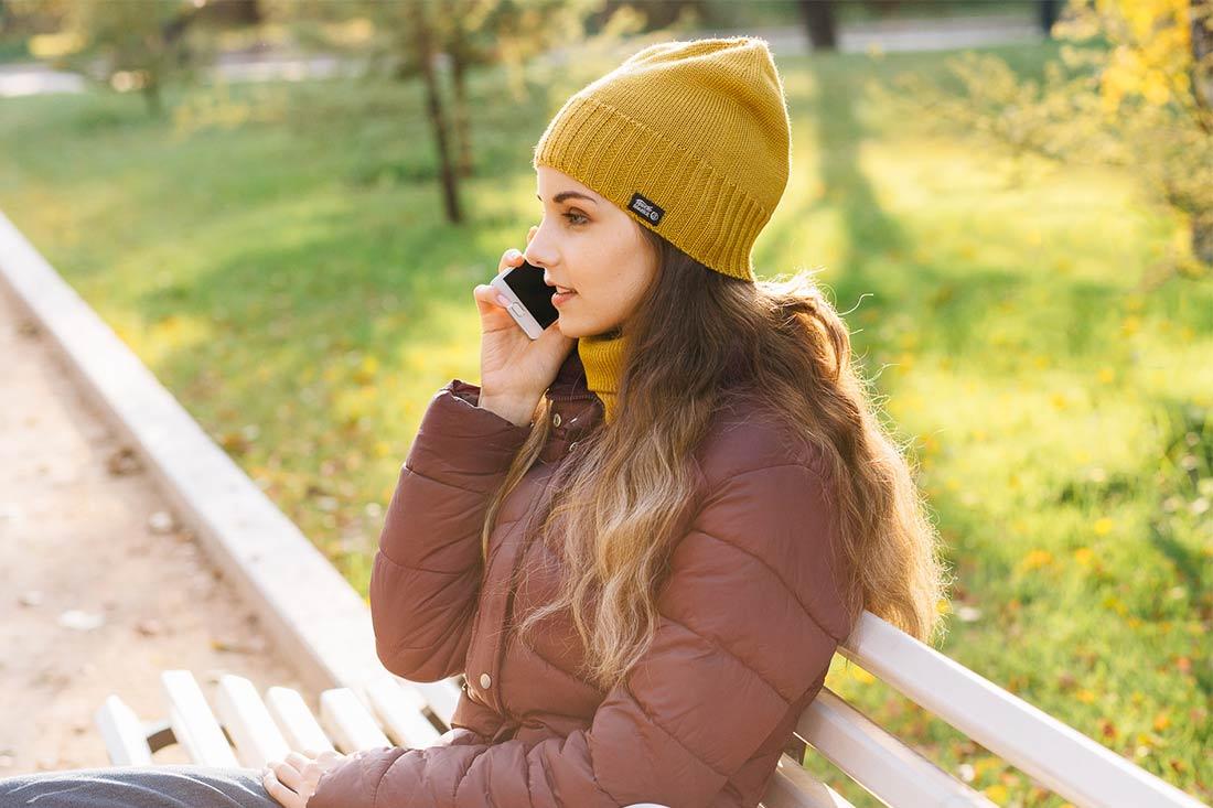 Молодая девушка сидит в парке на лавочке осенью. Вязаная шапка Стокгольм. Коллекция: осень-весна. Цвет горчичный.